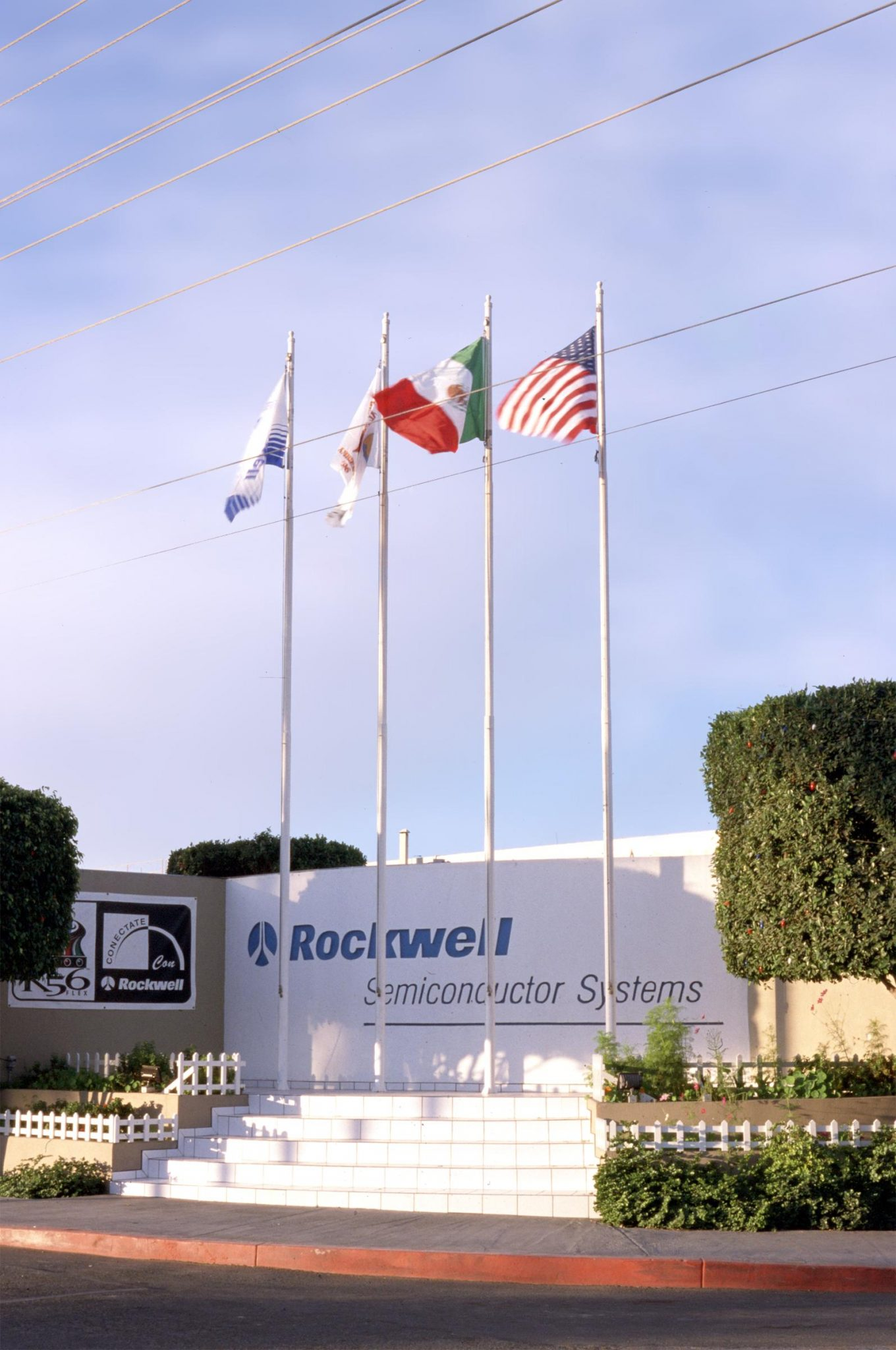 Eye level shot of Rockwell/ Skyworks industrial facility entrance and flags in Mexicali, Baja California