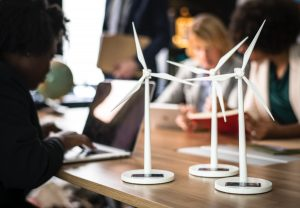Wind turbine scale model on top of desk surrounded by people.